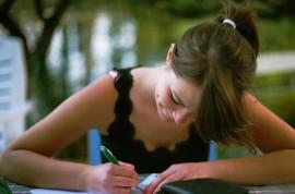 Eine junge Frau sitzt schreibend am Tisch