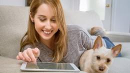 Frau mit Hund stöbert im iPad